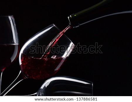 bottle and glasses with red wine on a black background - stock photo