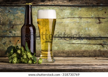 Bottle and mug full of beer with white foam with bunch of hops on wood background.  - stock photo