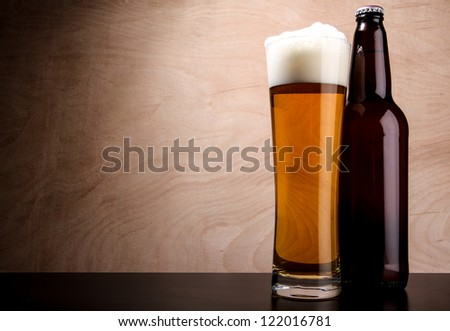 Bottle and tall glass with beer served on the table