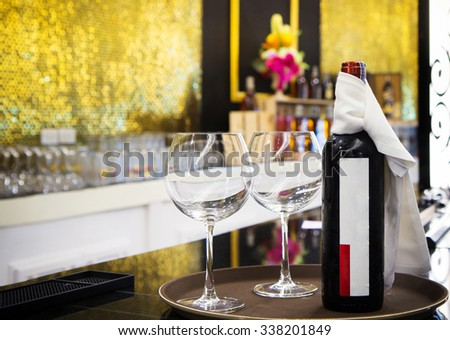 Bottle and two glasses of red wine together on a tray served
