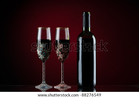 Bottle and two glasses of red wine with red background - stock photo