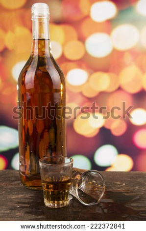 bottle and two glasses of rum whiskey alcohol on wooden table over defocused lights background - stock photo