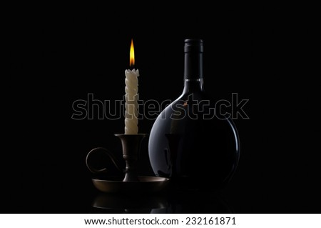Bottle, candle and glass of wine on black background