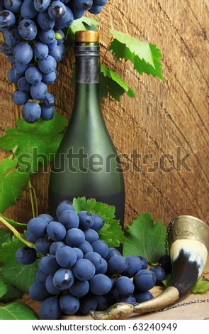 Bottle, drinking horn and bunch of grapes - stock photo