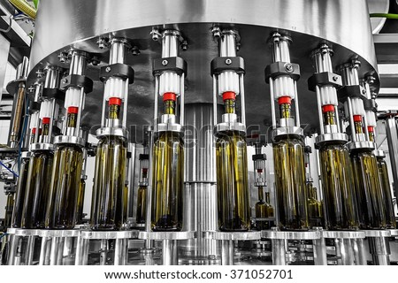 bottle filling,wine bottles filled with wine by an industrial machine in a wine factory - stock photo
