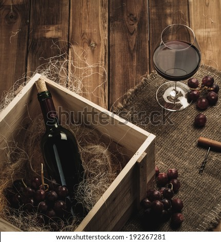 Bottle, glass and red grape on a wooden table  - stock photo
