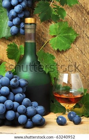 Bottle, glass of cognac (brandy) and bunch of grapes - stock photo