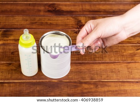 Bottle mixture of powdered milk bank in a dark wood. - stock photo