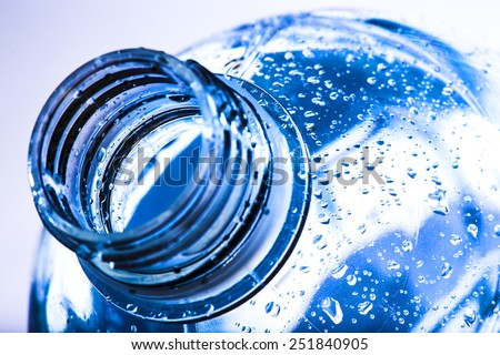 bottle neck with water drops on blue background  - stock photo