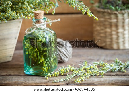 Bottle of absent or tincture of tarragon, absinthe healing herbs on old wooden table. Herbal medicine.