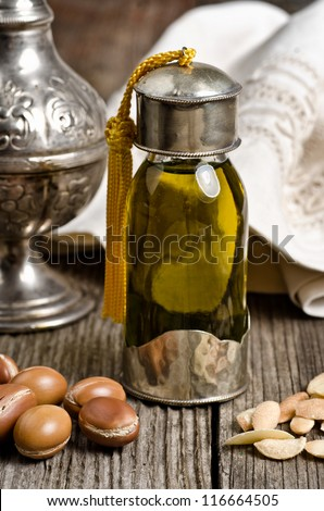 Bottle of argan oil and argan fruit. Argan oil is used for skincare products. - stock photo