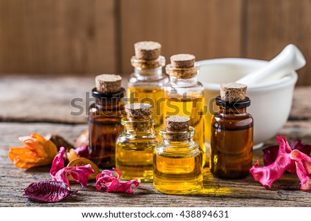 bottle of aroma essential oil with dry flower and mortar on wooden table, spa concept. - stock photo