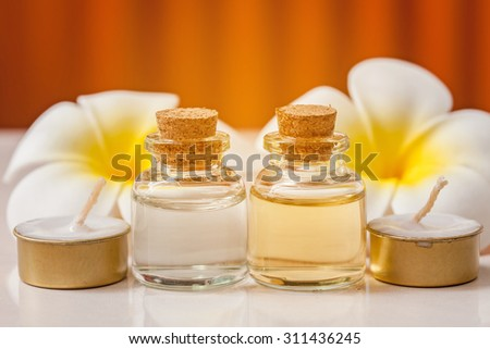 bottle of aroma essential oil with flower and candle on wooden background, spa concept. - stock photo