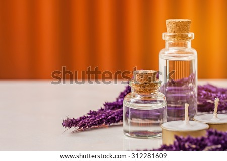 bottle of aroma essential oil with grass flower and candle on stone table, spa concept. - stock photo