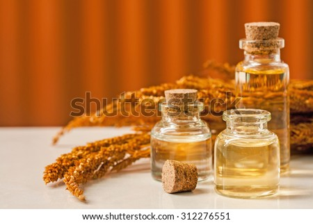 bottle of aroma essential oil with grass flower on stone table, spa concept. - stock photo