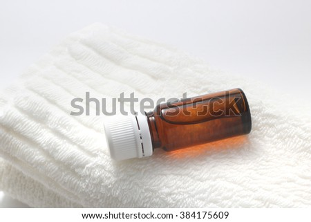 Bottle of aroma oil on the face towel. - stock photo