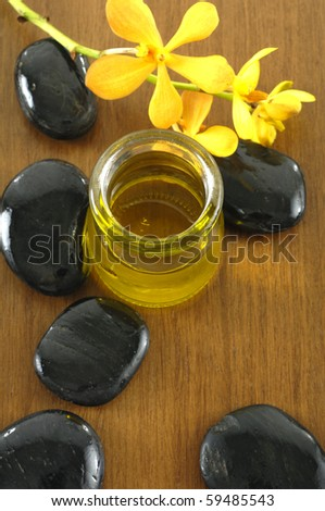bottle of aromatherapy oil and black stones on board - stock photo
