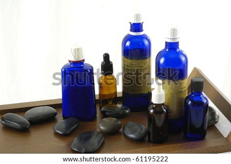 bottle of aromatherapy oil and black stones - relaxing treatment- - stock photo