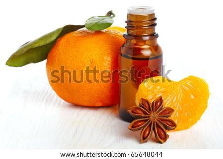 bottle of aromatic essence and fresh orange on white isolated background - stock photo