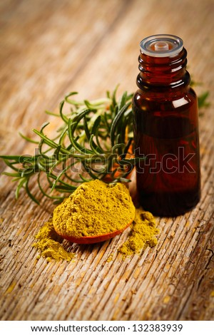 Bottle of aromatic essence oil, fresh and powdered rosemary - stock photo