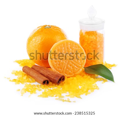 Bottle of bath salt with fresh orange, bar of soap and cinnamon isolated on white - stock photo