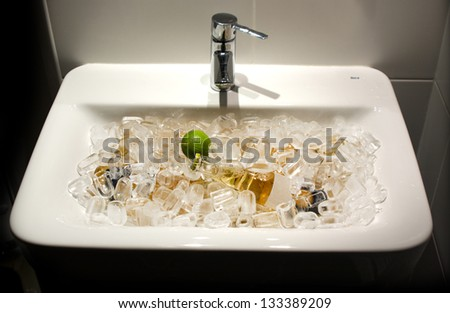 bottle of beer and a bottle of wine is in the sink in the ice - stock photo