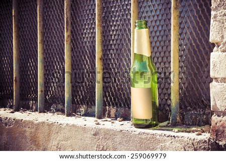 Bottle of beer left on the windowsill of an old window: alcoholism concept - stock photo