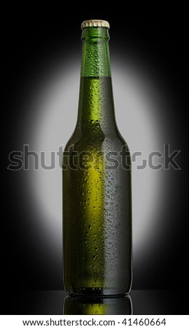 Bottle of beer on a black background with a grey spot - stock photo