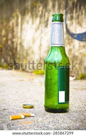 Bottle of beer resting on the ground with three cigarette's butts.Alcoholism and tobacco addiction concept - stock photo