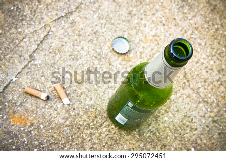 Bottle of beer resting on the ground with three cigarette's butts. Alcoholism and tobacco addiction concept - stock photo