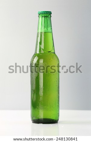 Bottle of Beer Small green beer cool bottle glass with bubble water drop  on a gray background.  - stock photo