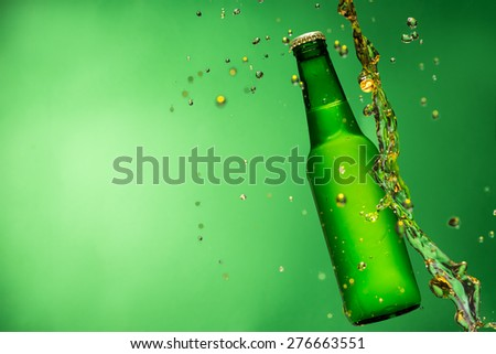 Bottle of beer with splash around on green background - stock photo