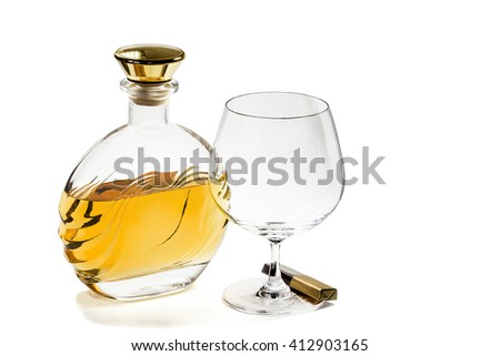 Bottle of brandy and empty snifter with chocolate on white background - stock photo