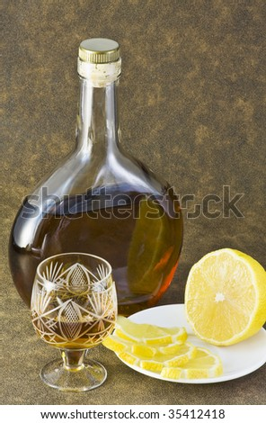 bottle of brandy and lemon slices on brown background