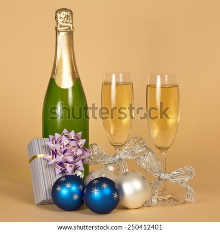 Bottle of champagne, and wine glasses with silver ribbons a romantic gift box, toys on a beige background