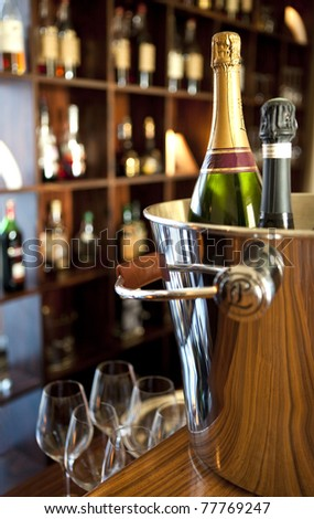 Bottle of champagne in a bucket, in a lounge - stock photo