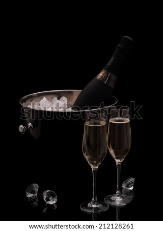 Bottle of champagne in bucket isolated on black with deco diamonds - stock photo