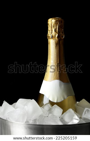 Bottle of champagne in bucket with ice, on black background