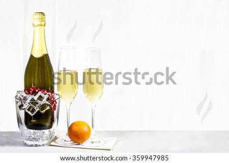 Bottle of champagne in ice bucket and two glasses with Mandarin are standing on a white napkin - stock photo