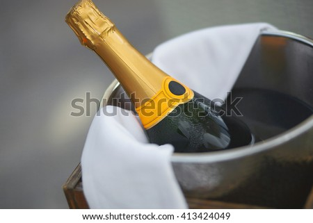 Bottle of champagne in ice bucket in restaurant. Close up picture with bokeh. - stock photo