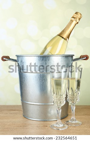 Bottle of champagne in metal ice bucket and two glasses on wooden table on light background