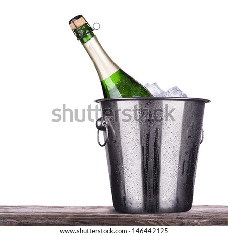 bottle of champagne in Metal ice bucket  on a wooden vintage table isolated on a white background