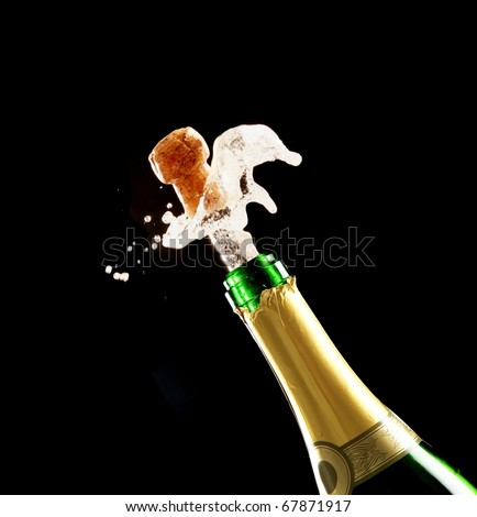 Bottle of champagne just opened with cork being expelled - stock photo