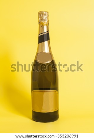 Bottle of champagne  on yellow background  - stock photo