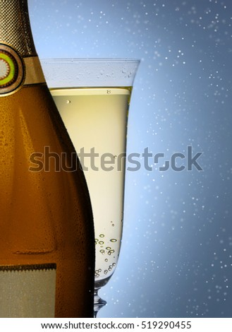 bottle of champagne with a glass closeup on blue background
