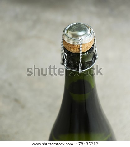 Bottle of champagne with cork over - stock photo
