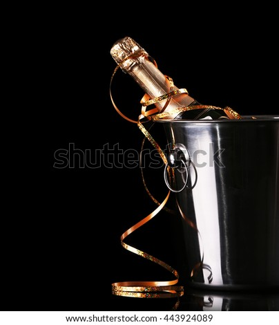 Bottle of champagne with ice in bucket on black background - stock photo