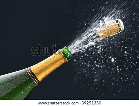 Bottle of Champagne with popping cork and Champagne spray on black background. - stock photo