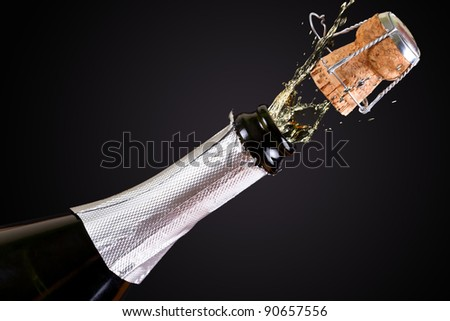 Bottle of champagne with splashes over black background - stock photo