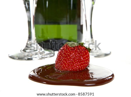 Bottle of Champagne with two flutes also a strawberry in chocolate - stock photo